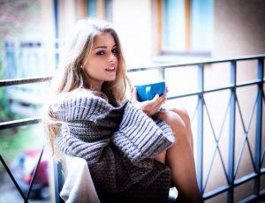 pretty girl drinking coffee beside balcony